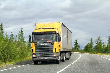 YAMAL, RUSSIA - AUGUST 5, 2012  Yellow Scania R340 semi-trailer truck at the interurban road