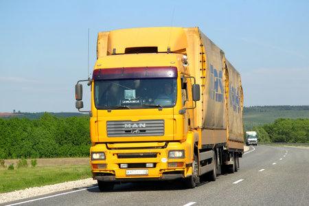 flatbed truck: TATARSTAN, RUSSIA - MAY 29, 2013: Yellow MAN TGA semi-trailer truck at the interurban road.