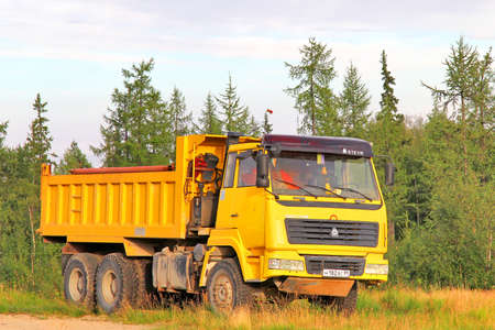 NOVYY URENGOY, RUSSIA - AUGUST 6, 2012: Yellow CNHTC Sinotruk dump truck at the city street.