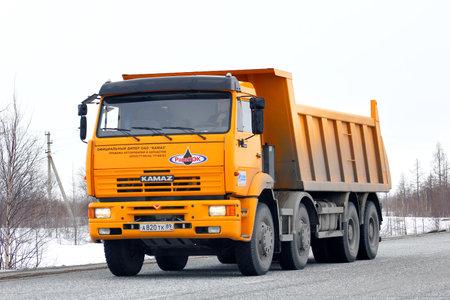 NOVYY URENGOY, RUSSIA - APRIL 23, 2013: Yellow KAMAZ 65201 dump truck at the interurban road.
