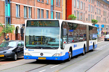 public transfer: AMSTERDAM, NETHERLANDS - AUGUST 10, 2014: Modern articulated bus Mercedes-Benz O530 Citaro G at the city street.