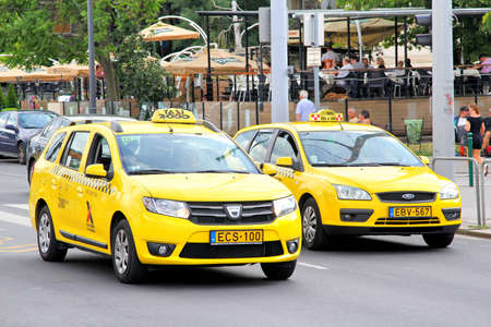 mpv: BUDAPEST, HUNGARY - JULY 23, 2014: Yellow taxi cars Dacia Logan and Ford Focus at the city street.