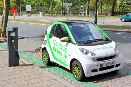 noiseless: BRUSSELS, BELGIUM - AUGUST 9, 2014: Modern electric minicar Smart Fortwo charging at the city street. Editorial