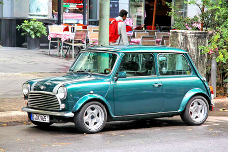 BERLIN, GERMANY - AUGUST 16, 2014: Green classic compact car Austin Mini Cooper at the city street. Editorial