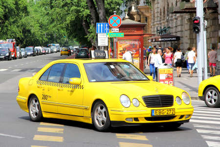 taxi: BUDAPEST, HUNGARY - JULY 23, 2014: Yellow taxi car Mercedes-Benz W210 E-class at the city street. Editorial