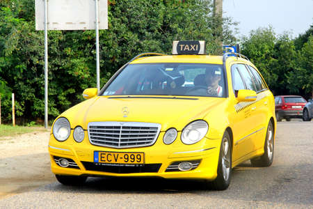 e 27: BUDAPEST, HUNGARY - JULY 27, 2014: Yellow taxi car Mercedes-Benz S211 E-class at the city street.
