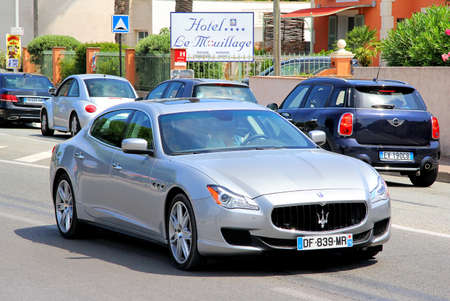 gr: SAINT-TROPEZ, FRANCE - AUGUST 3, 2014: Silver luxury sedan Maserati Quattroporte at the city street.
