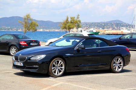 gr: SAINT-TROPEZ, FRANCE - AUGUST 3, 2014: Black convertible sports car BMW F12 6-series at the city street.