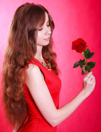 Beautiful young woman with a red rose over pink  photo