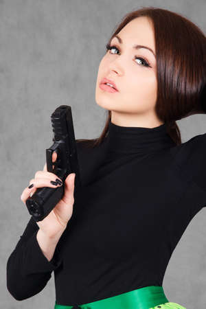 Portrait of a young attractive woman with a gun over grey background