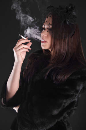 Portrait of a young attractive woman smoking a cigarette over black  photo