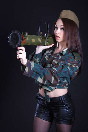 Portrait of a woman in a military uniform with a grenade launcher over black  photo