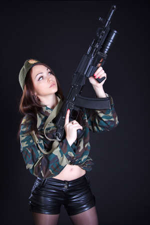 Portrait of a woman in a military uniform with an assault rifle over black background photo