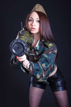 Woman in the military uniform with a grenade launcher over black background