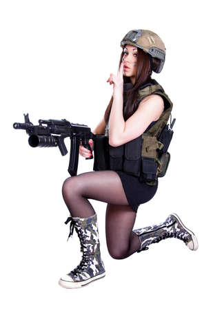 Woman in a military camouflage sitting with the assault rifle isolated over white background photo