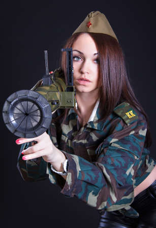 Woman in the military uniform with a grenade launcher over black  photo