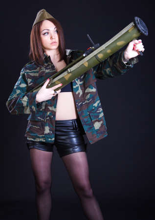 bazooka: Young woman in the military uniform with the bazooka over black