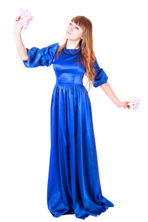 Young attractive woman in a long blue evening dress isolated over white background photo