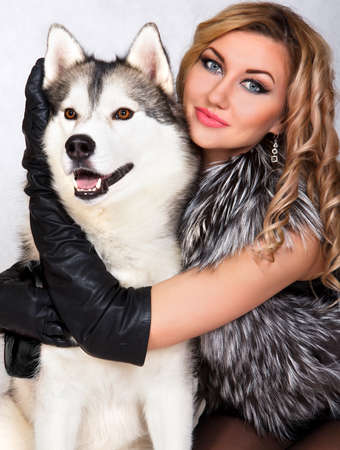leather coat: Portrait of a young attractive woman with a husky dog over grey background