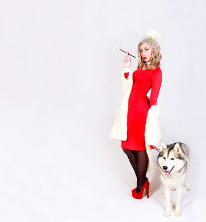 Portrait of a young attractive woman with a husky dog over grey background photo