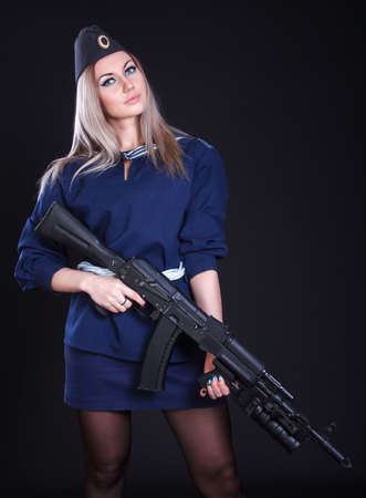 Woman in the marine uniform with an assault rifle over black background photo
