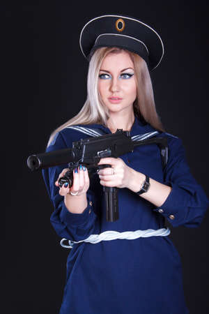 aslant: Beautiful young woman in a marine uniform with a submachine gun over black background