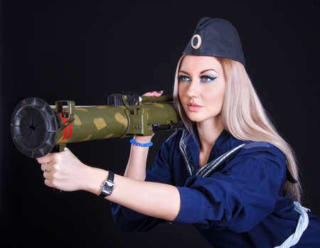 Beautiful young woman in a marine uniform with a grenade launcher over black  photo