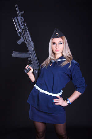 ak 74: Beautiful young woman in a marine uniform with an assault rifle over black