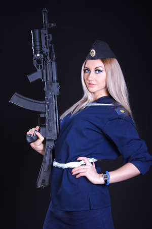cadet blue: Woman in the marine uniform with an assault rifle over black background Stock Photo