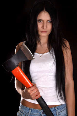 Young woman with a big axe over black background