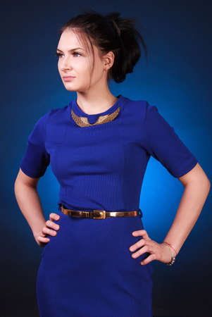 austere: Young attractive woman in a blue evening dress over blue background