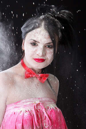 Young beautiful woman covered with a white powder over black background