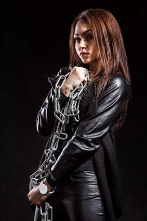 Beautiful young woman with chains over black background Stock Photo
