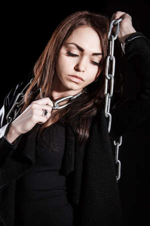 smother: Beautiful young woman with chains over black background Stock Photo