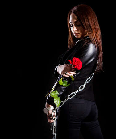 tomboy: Beautiful young woman with chains and a red rose over black background
