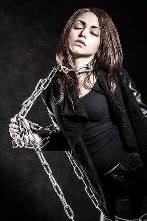 stifle: Young woman in a black clothes with a chain over dark background Stock Photo