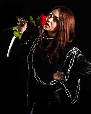 Beautiful young woman with chains and a red rose over black background