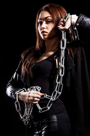 tomboy: Beautiful young woman with chains over black background Stock Photo