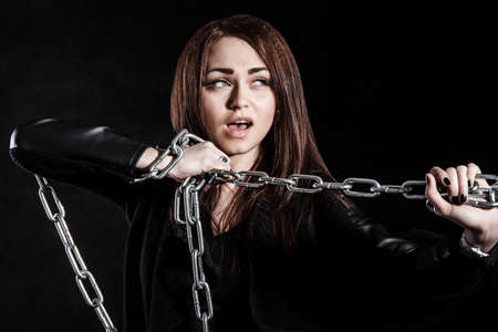 Beautiful young woman with a chain over black background Stock Photo
