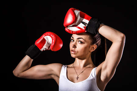 perspiration: Beautiful young woman in a red boxing gloves over black background