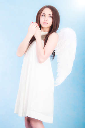 civility: Beautiful young angel over cyan background Stock Photo