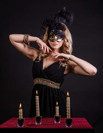 alight: Mysterious woman in a mask near the table with alight candles over black background