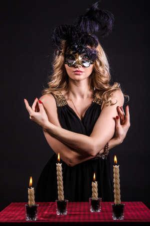 adivino: Misteriosa mujer en una m�scara cerca de la mesa con velas posan sobre el fondo negro
