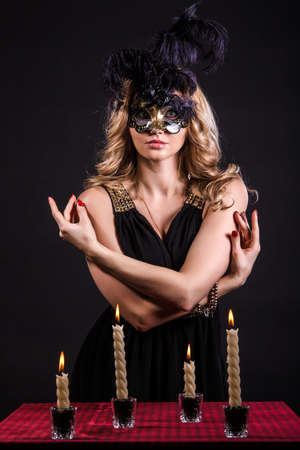 mysterious woman: Mysterious woman in a mask near the table with alight candles over black background