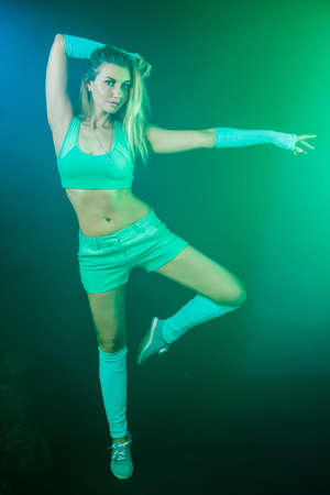 aside: Beautiful young gymnast between blue and green clouds of smoke