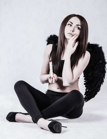 fallen angel: Beautiful young woman in a costume of the fallen angel holding a candle over grey background