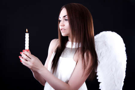 civility: Beautiful young angel with a candle over black background