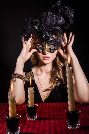 mascara de carnaval: Misteriosa mujer en una máscara cerca de la mesa con velas posan sobre el fondo negro