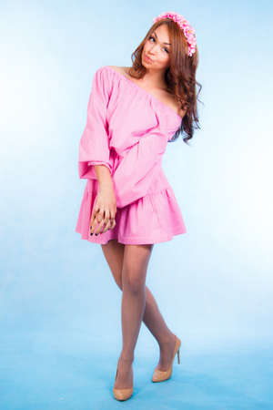 barbie: Cute young woman in a pink clothes over blue background
