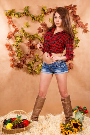 staying: Cute young woman staying in a hay at the background of maple leaves Stock Photo